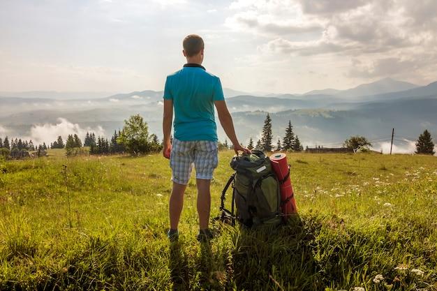 Турист с рюкзаком стоит в горах