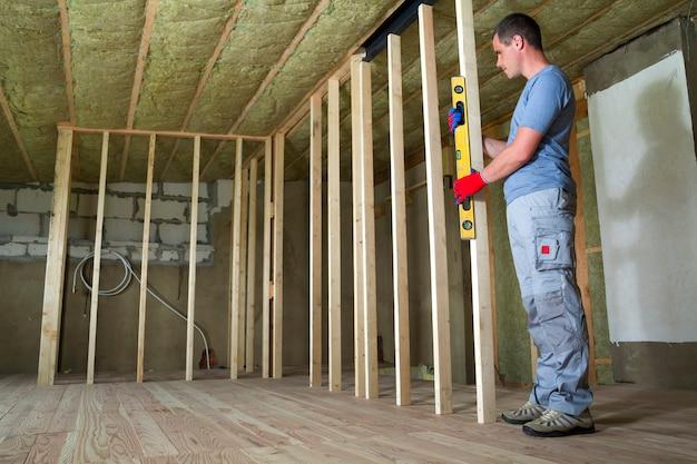 Интерьер мансардного помещения с изолированным потолком и дубовым полом на реконструкции. молодой профессиональный работник использует уровень, устанавливающий деревянную раму для будущих стен. концепция реконструкции и благоустройства.