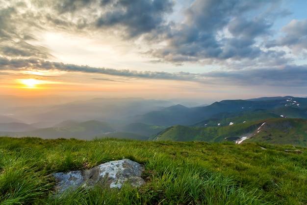 日の出の広い夏のマウンテンビュー。大きな岩と遠くの山並みと緑の草で覆われた丘の上の青い曇り空に輝くオレンジ色の太陽が朝の霧で覆われています。自然概念の美しさ。