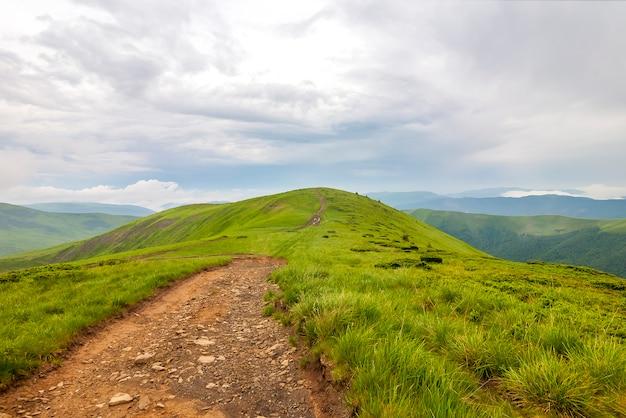 シャープな緑の山頂と劇的な雲の風景と空