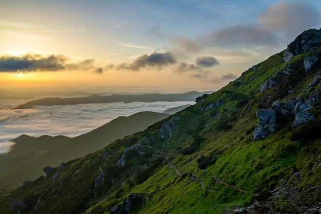 日の出の明るいオレンジ色の輝きと明るい朝空の下で霧の地平線に伸びる雪の雲のような低い白いふくらんでいる山の谷の素晴らしい景色。自然概念の美しさ。