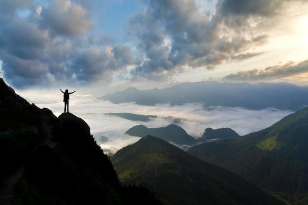 Широкая горная панорама. маленький силуэт туриста с рюкзаком на скалистой горе.