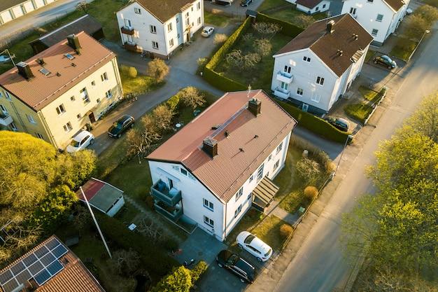 Вид с воздуха жилых домов с красными крышами и улиц с припаркованными автомобилями в сельской местности города. тихие пригороды современного европейского города.