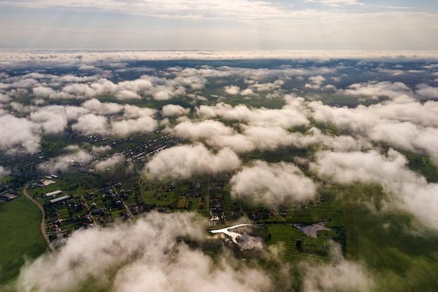 Вид с воздуха на белые облака над городом или деревней с рядами зданий и пышные улицы между зелеными полями в летнее время. сельский пейзаж сверху.