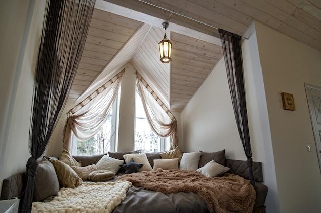 大きな柔らかい休憩所とモダンな家の広々とした廊下のインテリア。多くの枕と木製のロフト天井に明るい窓がある現代的な幅の広いソファ。