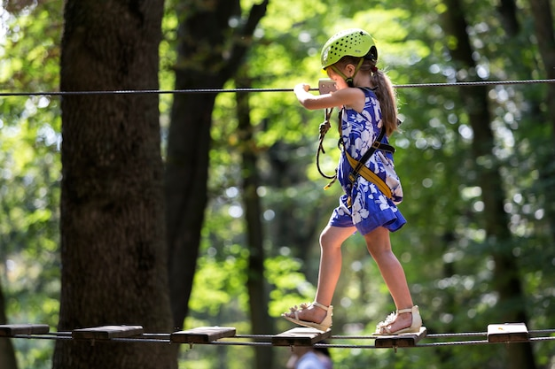安全ハーネスとカービン銃で接続されたヘルメットの若い子女の子。