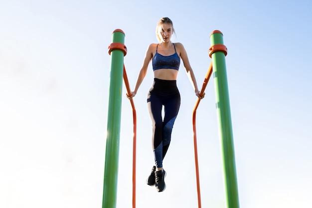 スタジアムコートで屋外の金属棒にフィットネス運動を行う若い陽気なアスリート女性。