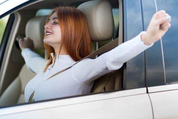 若い赤毛の女性ドライバーが幸せそうに笑って車で休んでいるシートベルトで固定されています。