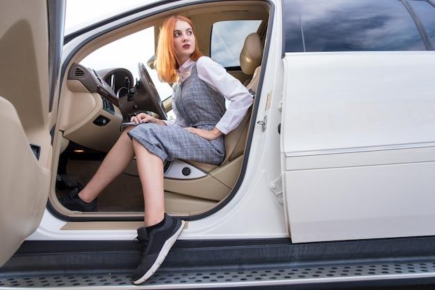 Довольно модная молодая женщина водитель в повседневной одежде и кроссовки, сидя в дорогой новый автомобиль.