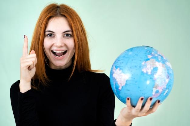 Портрет счастливой молодой женщины, держащей географический глобус мира в ее руках. путешествия и концепция защиты планеты.