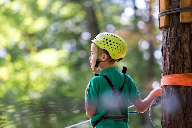 安全ハーネスとヘルメットの若い男の子は、公園のロープウェイでケーブルにカービン銃で接続されています。