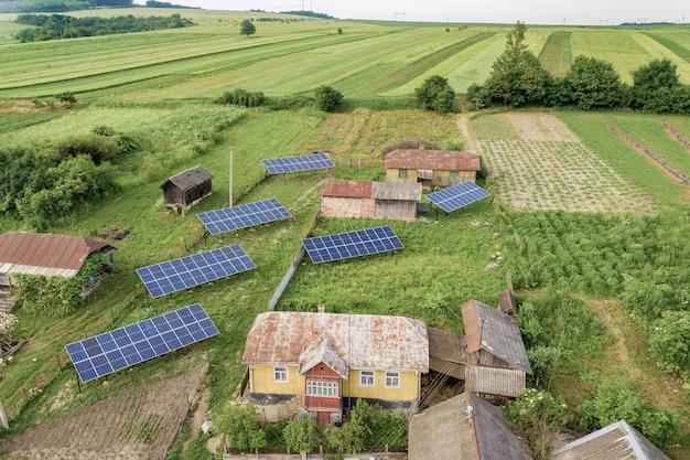 緑の農村地域における太陽電池パネルの空中トップダウンビュー。