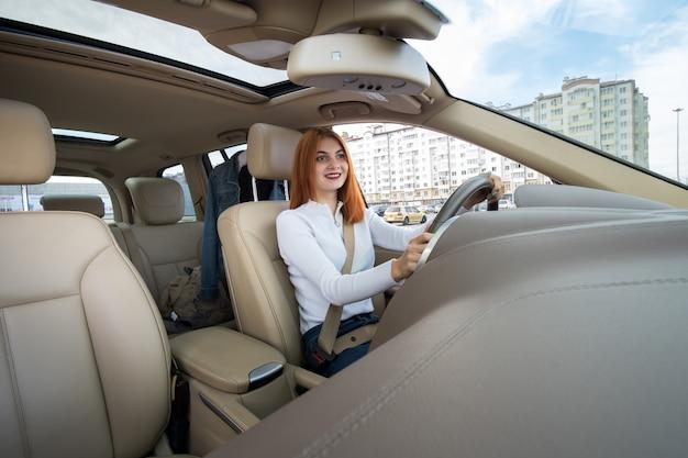 幸せそうに笑って車を運転するシートベルトで固定された若い赤毛の女性ドライバーの広角ビュー。