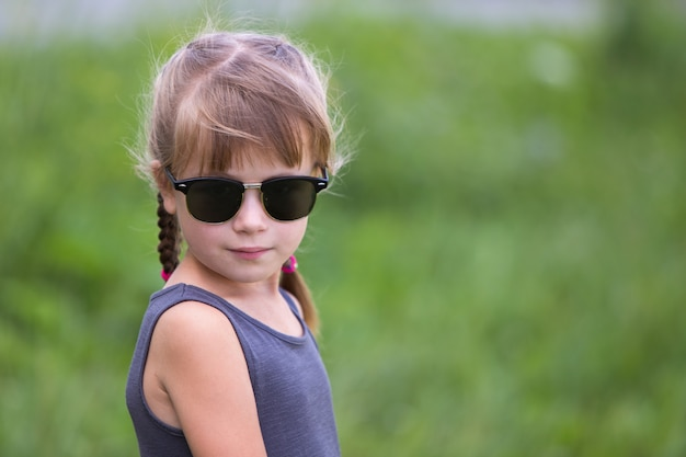 夏の屋外の髪のお下げとかわいい子少女の肖像画。