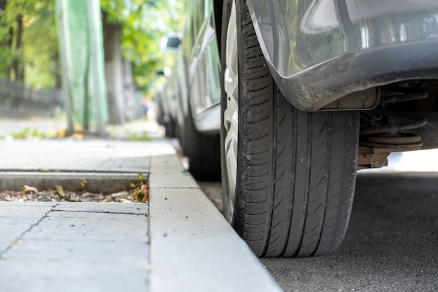 Крупный план колеса автомобиля припарковал около обочины на стороне улицы на месте для стоянки.