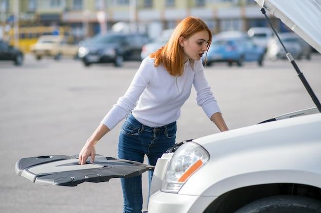 Молодой усиленный водитель женщины стоя около сломленного автомобиля с открытым клобуком.
