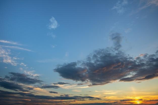 青い夕焼け空は白いふくらんでいる雲で覆われています。