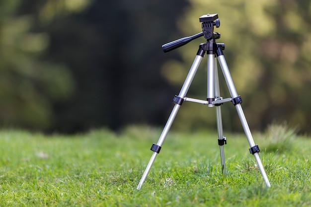 明るい日当たりの良い夏の日に新鮮な草で覆われた牧草地で一人で立っている孤立したアルミニウム光沢のある三脚。