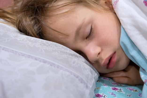 少し口を開けて、自宅のベッドで寝ている髪の周りに散らばっているかわいい子少女の顔のクローズアップ。