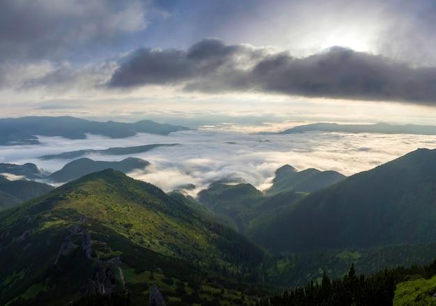 日の出の明るいオレンジ色の光と明るい朝の空の下で霧の地平線に伸びる雪の雲のような低い白いふくらんで覆われた山の谷の素晴らしい景色。自然概念の美しさ。