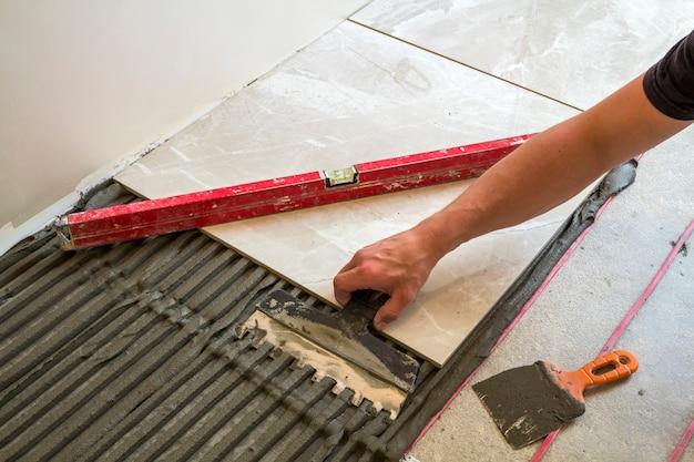 床タイルを取り付ける労働者の手