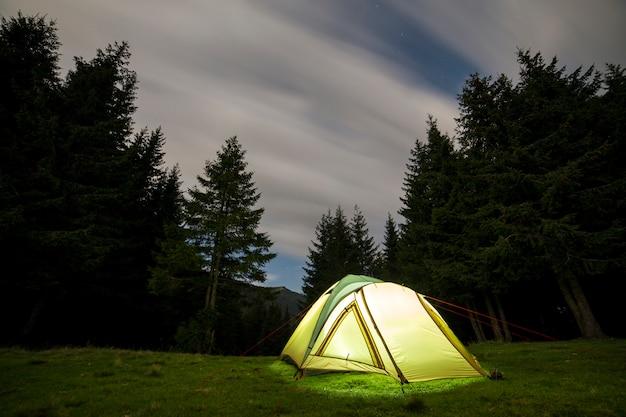 夜の夏のキャンプ。遠い山の緑のクリアリングに照らされた観光テント。