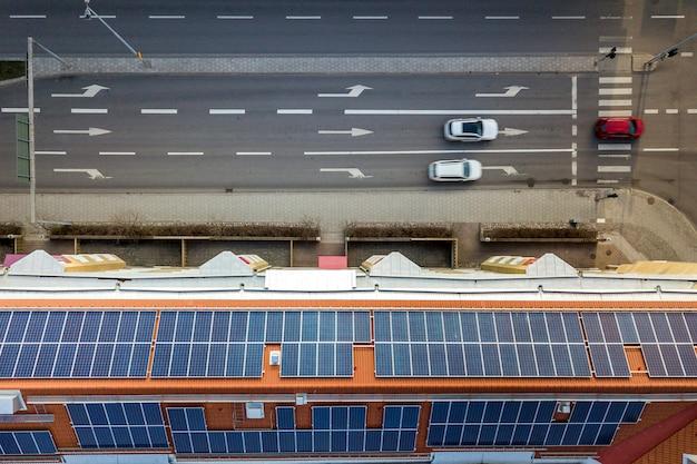 アパートの建物の屋根の上の太陽光発電太陽光発電パネルシステムの空撮。再生可能な生態学的なグリーンエネルギー生産の概念。