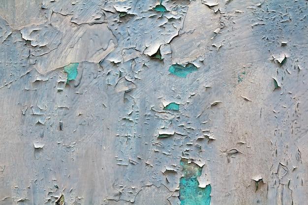 古いひびの入った抽象的なグランジビンテージテクスチャコピースペース背景、レトロなパターン。白い不規則な斑点は、水色のコンクリートまたは木製の壁または天井の平らな面の剥離をペイントします。