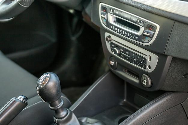 豪華な車の黒革のインテリア。ぼやけたダッシュボードの背景にハンドブレーキマニュアルブレーキとギアシフトスティックのクローズアップの詳細。輸送、デザイン、近代的な技術コンセプト。