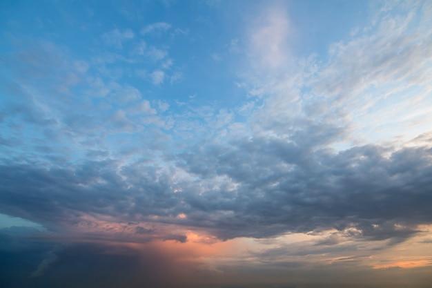 日の出または日没の空のパノラマ。澄んだ空に明るいオレンジ色の黄色い太陽に照らされた濃い青の雲の美しい景色。自然の美しさと力、気象学、気候変動のコンセプト。