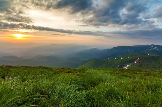 日の出の広い夏のマウンテンビュー。緑の草が茂った丘の柔らかい草と朝の霧で覆われた遠くの山脈の上に青い曇り空を上げる輝くオレンジ色の太陽。自然概念の美しさ。