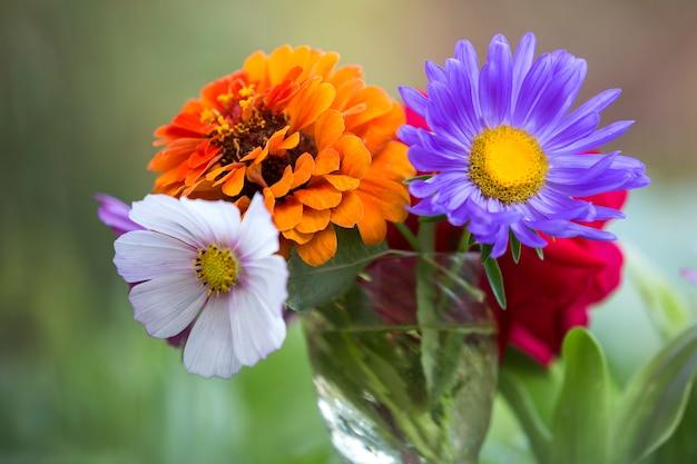 屋外の透明なガラスの花瓶に美しい秋の明るい色とりどりの野の花の組成のクローズアップ。