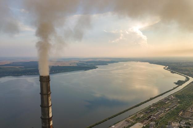 石炭発電所からの灰色の煙が付いている高い煙突のパイプ
