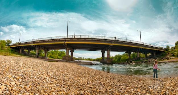 小さな女の子は街の大きな橋の近くの川で遊んでいます