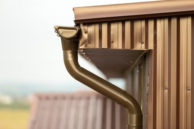 金属板サイディングと雨どい雨システムと屋根のコテージの家のコーナーのクローズアップの詳細。