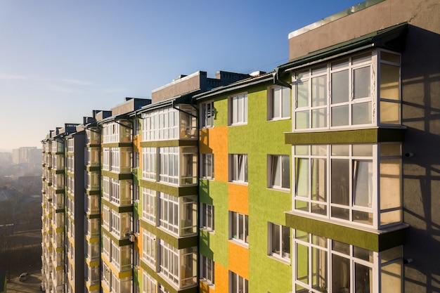 Вид с воздуха на высокий жилой жилой дом с множеством окон и балконов.