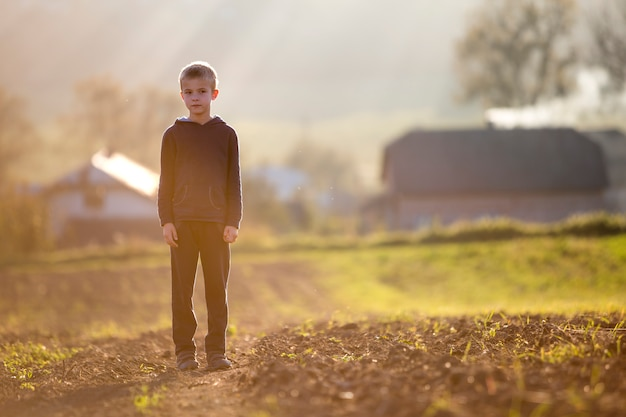 夏の終わりまたは秋の晴れた日に収穫後フィールドに一人で立っている若いブロンドの深刻な疲れている子少年。