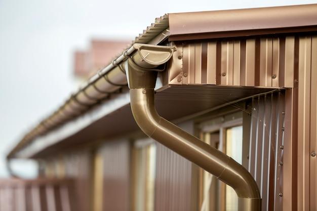 金属板の下見張りと雨どい雨システムと屋根のコテージの家のコーナーのクローズアップの詳細。