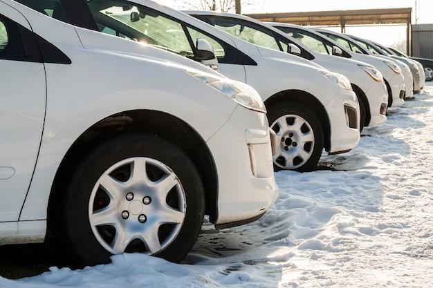 多くの駐車中の車。カーディーラーの駐車場に新車の行。販売市場テーマの車。