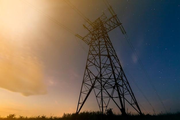 電気のコンセプトの伝送と長距離分配。濃い青の星空に伸びる送電線のある高電圧塔の斜めビュー。