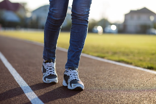 スポーツスニーカーとブルージーンズの屋外スポーツコートでランニングレーンで女性の足のクローズアップ。