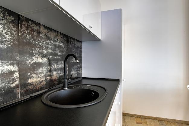 Интерьер современной просторной кухни с белой современной мебелью, черной керамической плиткой на стене и темной гранитной раковиной с водопроводным краном.