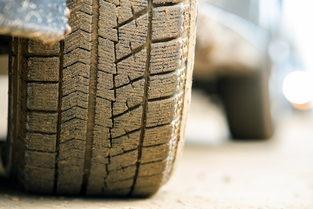 黄色の泥で覆われたゴム製タイヤで汚れた車のホイールのクローズアップ。