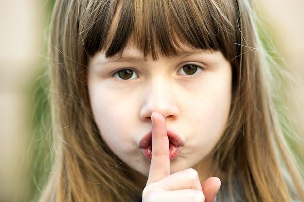 Портрет довольно ребенка девушка с серыми глазами и длинные светлые волосы, держа палец на ее губах с тихим вздохом. милый женский парень на теплый летний день снаружи.