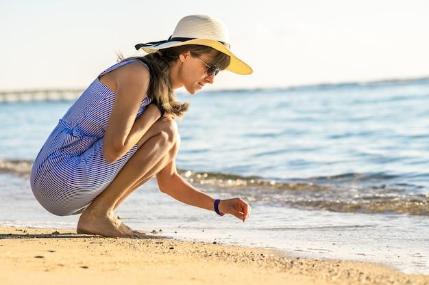 Молодая женщина в летней одежде, писать что-то на песке морского пляжа.