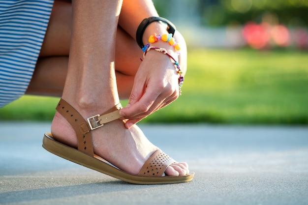 日当たりの良い天気で歩道に彼女の開いている夏のサンダルの靴を結ぶ女性の手のクローズアップ。