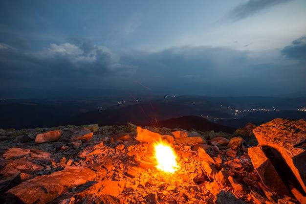 Яркий огонь горит на вершине скалистой горы под голубым облачным небом.