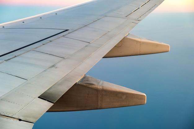 晴れた朝に海の風景の上を飛んでいる航空機の白い翼の飛行機からの眺め