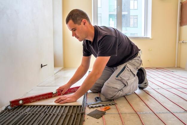 若年労働者の瓦職人が赤い電気ケーブルワイヤーシステムを加熱してセメントの床にレバーを使用してセラミックタイルをインストールします。改築、改修、建設、快適な暖かい家のコンセプト。