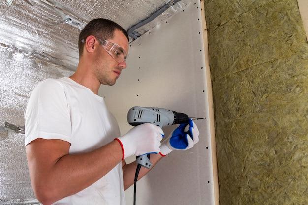 絶縁に取り組んでいるドライバーでゴーグルの労働者。壁の梁に乾式壁、木枠のロックウールスタッフを絶縁。快適な暖かい家、経済、建設、改修のコンセプト。